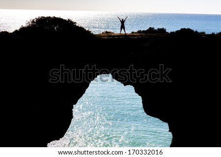 Woman standing in a winning position on a cliff