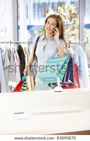 Woman standing in clothes shop, holding shopping bags, speaking on mobile phone, smiling.?