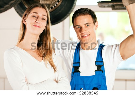 Woman standing in front of her car which is lifted on an auto hoist, a mechanic doing a repair underneath the auto - stock photo