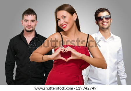 Woman Standing In Front Of Men Making A Heart Shape Sign On Gray Background