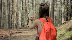 Woman standing in middle of forest, using navigation app on smartphone, following route with help of map, looking at device screen, using smartphone navigation while losing yourself in forest