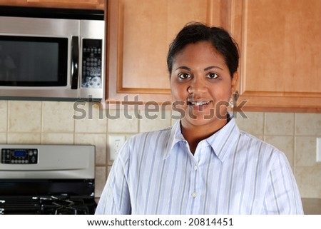 Woman standing in the kitchen of her home - stock photo
