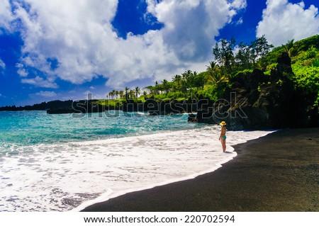 Woman standing in the waves on a black sand beach on the Road to Hana, Maui, Hawaii, USA