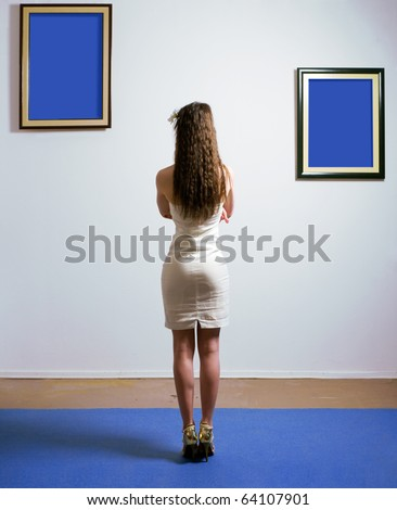 Woman standing inside a gallery infront of two picture frames. Images are fill with blue color