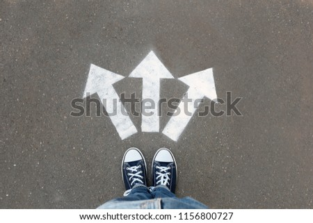 Woman standing near arrows on asphalt, top view. Choice concept #1156800727