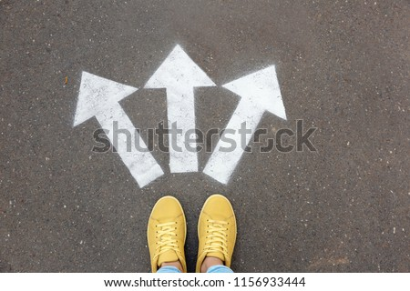 Woman standing near arrows on asphalt, top view. Choice concept #1156933444