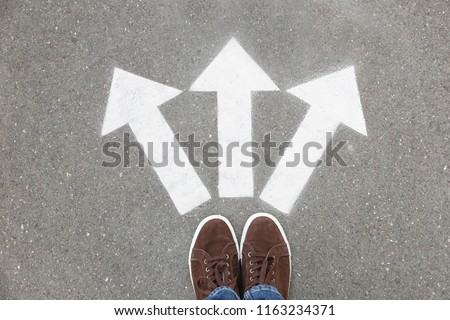 Woman standing near arrows on asphalt, top view. Choice concept #1163234371