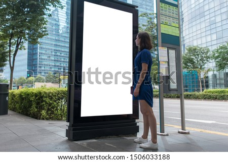 Woman standing near blank advertising lightbox on the bus stop, mock up.