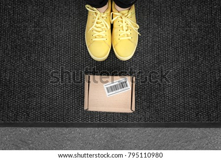 Woman standing near delivered parcel on doormat, closeup
