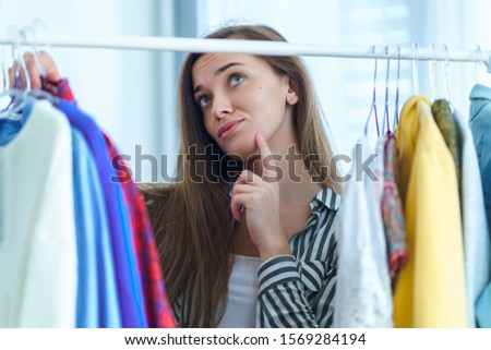 Woman standing near wardrobe rack full of clothes on hangers, having difficult choice not knowing what to wear on. Nothing to wear concept. Female choosing and searching clothes for special occasion.