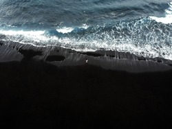 Woman standing on a black sand beach of Los Gigantes in Tenerife, Canary islands, Spain