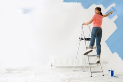 Woman standing on a ladder is applying blue paint to the wall in her house using a paint-roller.