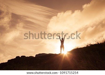 Photo of Woman standing on a mountain top with arms in the air celebrating. Victory and winning concept.