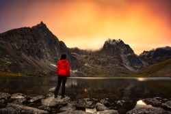 Woman Standing on a Rock at an Alpine Lake surrounded by Rugged Mountains during Fall in Canadian Nature. Dramatic Colorful Sunset Artistic Render. Taken in Tombstone Territorial Park, Yukon, Canada.