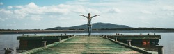 Woman standing on a wooden jetty  enjoying the sunshine with arms up. Woman on a pier on the lake greeting the sun with arms wide open. Authentic image, cinematic analog film look. Banner wide format.
