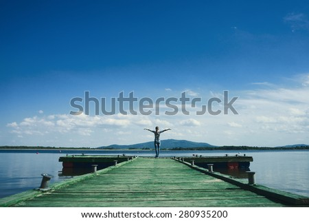 Woman standing on a wooden jetty enjoying the sunshine with arms up. Woman on a pier on the lake greeting the sun with arms wide open.