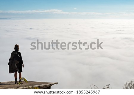 Woman standing on a wooden platform and enjoying the view of fog covered valley below. Hiking, achievement, expectation, optimism and self-reflection concepts. Foto stock ©
