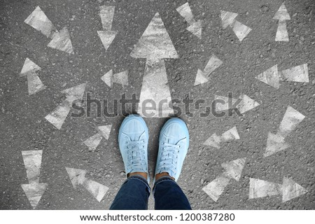 Woman standing on asphalt road with arrows pointing in different directions. Concept of choice Stock photo ©