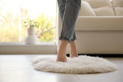 Woman standing on faux fur rug in living room, closeup. Space for text