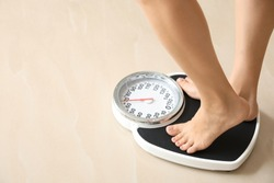 Woman standing on floor scales indoors, space for text. Overweight problem