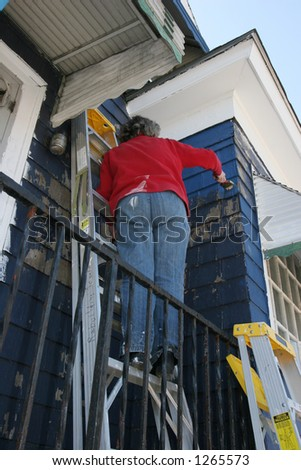 woman standing on ladder painting exterior of house - stock photo