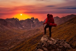Woman Standing on Rocks looking at Scenic Mountain Peaks and Valley during Fall in Canadian Nature. Dramatic Twilight Sky Artistic Render. Landscape in Tombstone Territorial Park, Yukon, Canada.