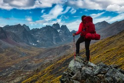 Woman Standing on Rocks looking at Scenic Mountain Peaks and Valley during Fall in Canadian Nature. Colorful Cloudy Sky Artistic Render. Landscape in Tombstone Territorial Park, Yukon, Canada.