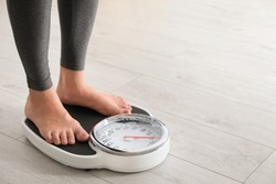 Woman standing on scales indoors, space for text. Overweight problem