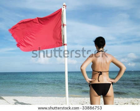 woman standing on te beach near a red flag on the sea meaning that swimming is dangerous and prohibite