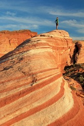 Woman standing on the Fire Wave rock at sunset, Valley of Fire State Park, Nevada, USA