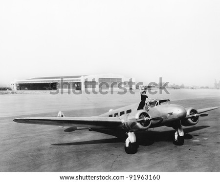 Woman standing on the propeller of an airplane waving