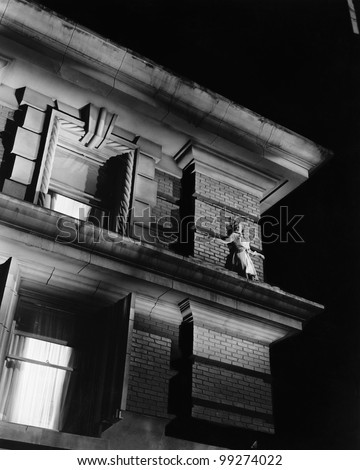 Woman standing on the top of a building on a ledge