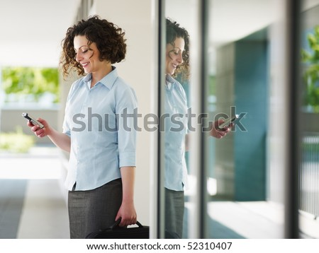 woman standing out of office building and reading emails on mobile phone. Horizontal shape, Copy space