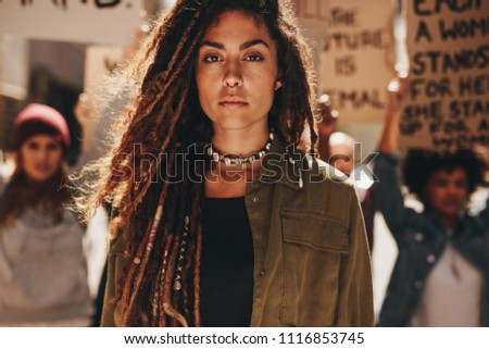 Woman standing outdoors in front of demonstrators on road. Female protesting with group of activists outdoors.