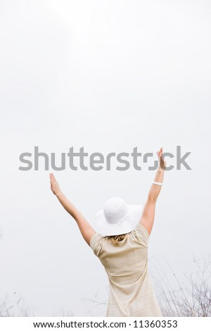 Woman standing outside with her arms up in the air with her back to the camera