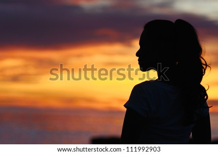 Woman standing silhouetted against the sunrise.