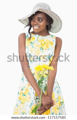 Woman standing wearing a floral dress while holding flowers