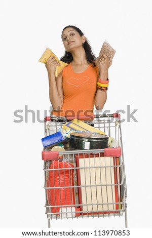 Woman standing with a shopping cart and showing packets