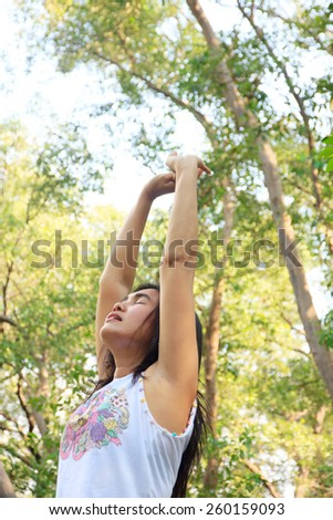 woman standing with arms open and eyes closed to breath the clean air from a spring forest
