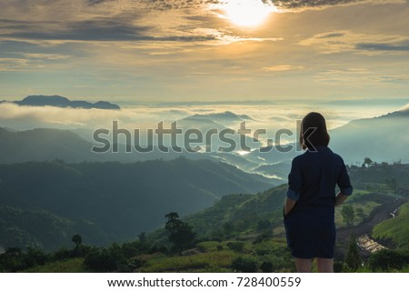 Woman standing with her hand in the pocket on the mountain top looking at panoramic view of mountain range in the mist under the sunrise