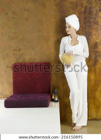 Woman standing with sponge, head wrapped in towel, looking away