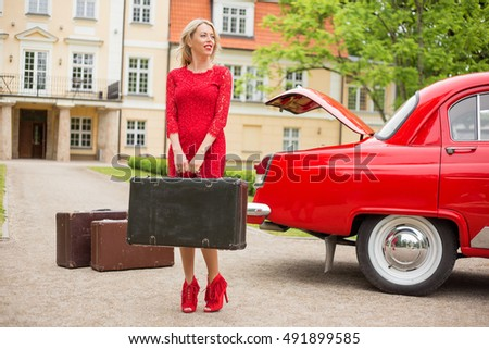 Woman standing with suitcase next to retro car