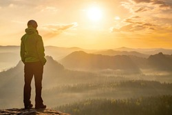 Woman stands alone on the peak of rock. Hiker watching to autumn Sun at horizon . Beautiful moment the miracle of nature. Colorful mist in valley. Man hike. Person silhouette stand