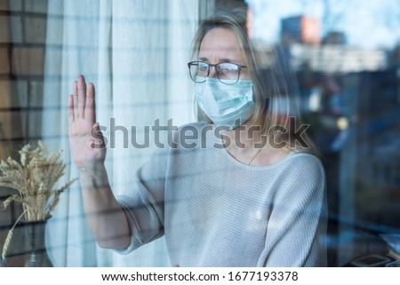 woman stands and looks out the window, self-isolation, prevention of corona virus Stock photo ©