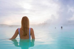 Woman stands back and enjoys spa in hot spring Blue Lagoon in Iceland. Early morning scenery