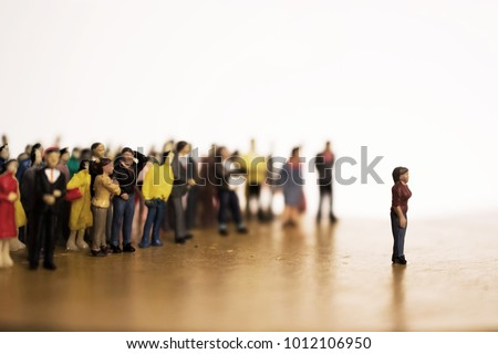 Woman stands in front of crowd or mob. Large group of people vs. one individual.  There are leaders and followers. One against many. Stand apart from the crowd. #1012106950