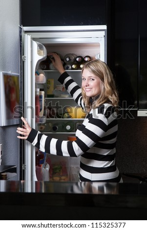 Woman stands in front of the opened fridge in the kitchen