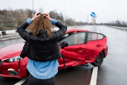 Woman stands near a broken car after an accident. call for help. car insurance