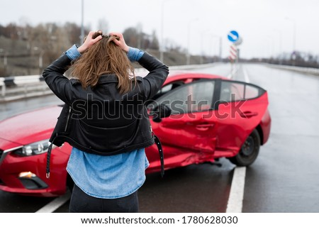 Woman stands near a broken car after an accident. call for help. car insurance Stock photo ©