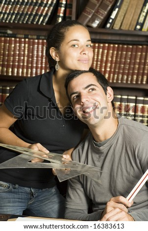 Woman stands next to man while they are studying at the library. They are leaning against each other. Horizontally framed photo.